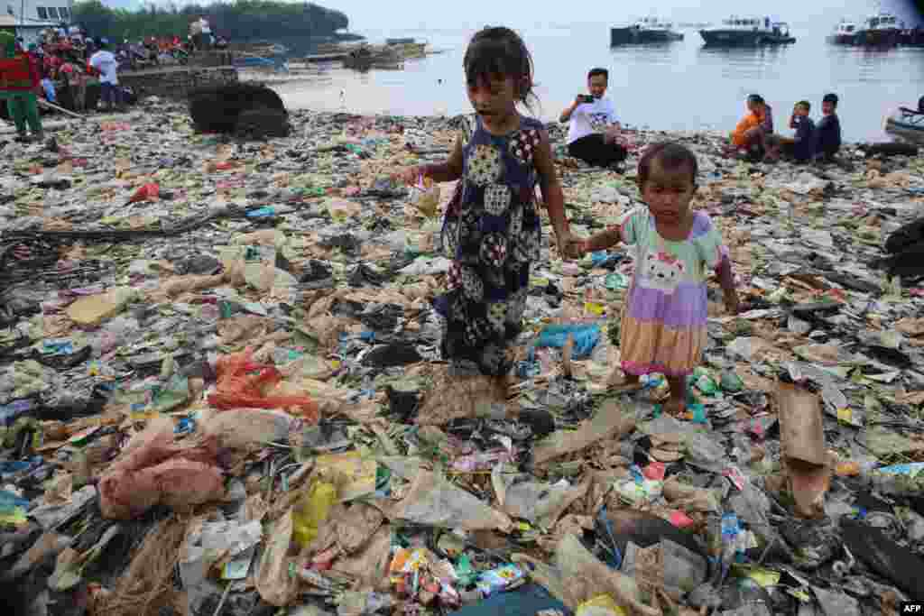 Children walk on garbage during an annual Lampung bay clean-up event in the Sukaraja village in the Bumi Waras subdistrict of Bandar Lampung, Indonesia.