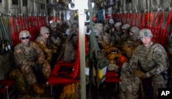 FILE - In this photo provided by the U.S. Air Force, soldiers from the 89th Military Police Brigade, and 41st Engineering Company, 19th Engineering Battalion, Fort Riley, Kansas, arrive at Valley International Airport in Harlingen, Texas, Nov. 1, 2018.