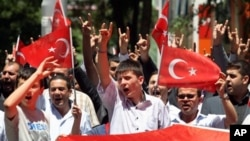 Turks hold national flags as they march in Ankara, Turkey to protest the killings of soldiers , Wednesday, June 20, 2012, a day after Kurdish rebels attacked Turkish military units with mortars and rocket-propelled grenades in the Daglica area of Hakkari