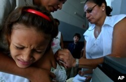 FILE - A girl is vaccinated against measles at a Health clinic in Managua, Nicaragua, Nov, 30, 2005.