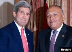 U.S. Secretary of State John Kerry, left, greets Egypt's Foreign Minister Sameh Shoukry in Cairo October 12, 2014.