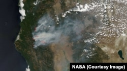 Smoke rising from wildfires burning in Northern California, as taken by NASA satellites, Aug. 6, 2015.