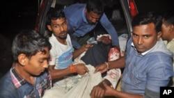 Warga membawa seorang pria yang terluka pasca serangan terhadap sebuah masjid di Bogra, Bangladesh Kamis (26/11).