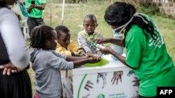 Un travailleur enseigne à plusieurs enfants comment se laver correctement les mains à l'entrée de l'hôpital Mbagathi de Nairobi, au Kenya, le 18 mars 2020. (Photo: LUIS TATO / AFP)