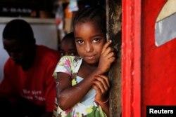 Une petite fille regarde derrière une porte à Dakar, au Sénégal, le 31 janvier 2011.