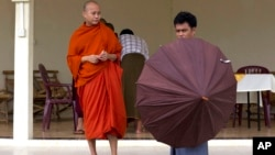 A Buddhist devotee holds an umbrella for controversial Buddhist monk Wirathu (L), who is accused of instigating sectarian violence between Buddhists and Muslims through his sermons, , near Rangoon, Burma, June 14, 2013.