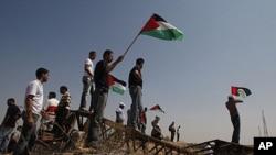 手举巴勒斯坦旗帜的巴勒斯坦人在加沙和以色列边界抗议时的情景