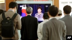 People at the Seoul Train Station watch a live television program showing South Korean President Park Geun-hye explain her decision to dismantle the Coast Guard after last month's deadly ferry incident, in Seoul, South Korea, May 19, 2014.