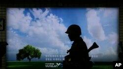 韩国军人在首尔地铁站的反恐演习中走过广告牌(2015年8月19日)