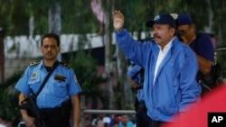 Escorté par un de ses gardes de sécurité armés, le président nicaraguayen Daniel Ortega, à droite, à Managua, au Nicaragua, le samedi 7 juillet 2018. (AP Photo / Alfredo Zuniga)