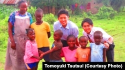 Japanese interns Tomoyuki Tsutsui and Keitaro Kakoi with residents of Kisumu, Kenya, where a water project will bring clean water to residents.