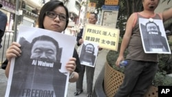Pro-democracy protesters carry portraits of detained Chinese artist Ai Weiwei in Hong Kong, April 10, 2011
