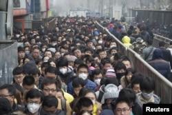 2015年12月8日,在北京首次发布空气污染红色警报后,乘客在地铁站排队。