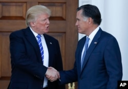 FILE - President-elect Donald Trump and Mitt Romney shake hands as Romney leaves Trump National Golf Club Bedminster in Bedminster, N.J., Nov. 19, 2016.