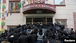 FILE - Riot police block the entrance of a pro-Kurdish People's Democratic Party (HDP) office in order to prevent party members from going out for a demonstration in the southeastern city of Diyarbakir, Turkey, Jan. 21, 2018.