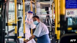 A health worker gestures to a man (R) receiving a checkup on a mobile health clinic on a bus during a medical checkup and contact tracing campaign in Yangon on September 9, 2020, as authorities work to halt the spread of the Covid-19 coronavirus. - Myanma