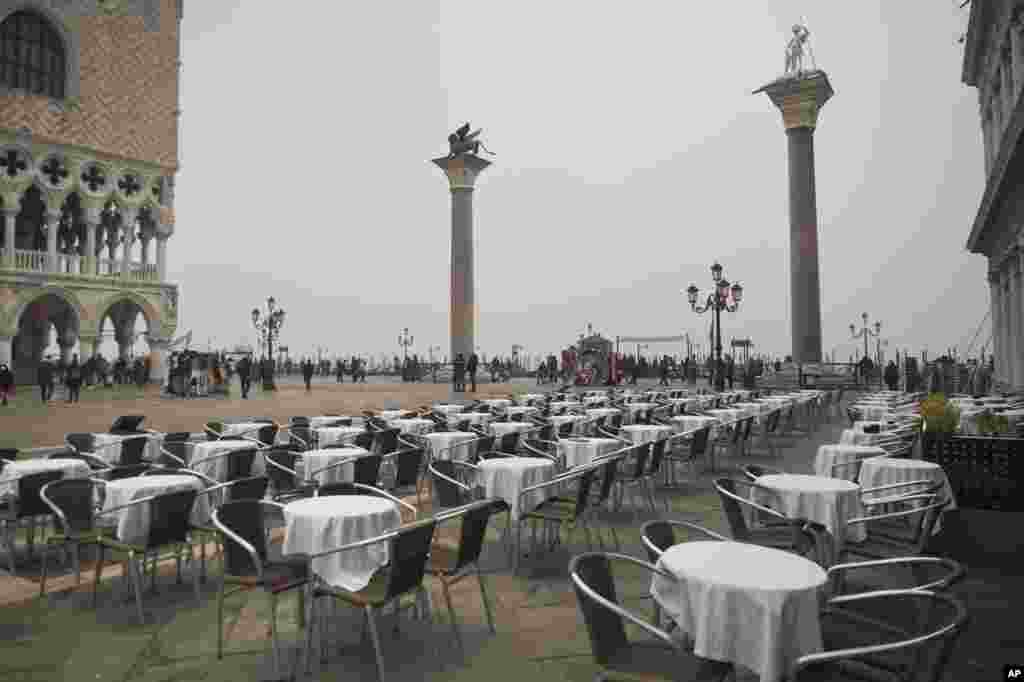 Empty tables sit in St. Mark's square in Venice, Italy. Italy has been scrambling to check the spread of Europe's first major outbreak of the new viral disease amid rapidly rising numbers of infections and calling off the popular Venice Carnival and closing tourist attractions.