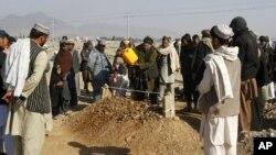 Seorang warga Afghanistan menuangkan air ke makam seorang korban korban akibat bentrokan pejuang Taliban dan pasukan Afghanistan di Bandara Kandahar, Afghanistan (10/12).