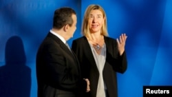 Serbian Foreign Minister Ivica Dacic greets European Union foreign policy chief Federica Mogherini as she arrives for an OSCE Ministerial Council meeting in Belgrade, Serbia, Dec. 3, 2015.