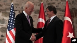U.S. Vice President Joe Biden, left, and Turkish Prime Minister Ahmet Davutoglu shake hands before a meeting in Istanbul, Turkey, Nov. 21, 2014.