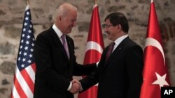 U.S. Vice President Joe Biden, left, and Turkish Prime Minister Ahmet Davutoglu shake hands before a meeting in Istanbul, Turkey, Nov. 21, 2014.