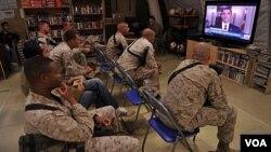 Infantes de Marina de EE.UU., miran un mensaje del presidente Obama en televisión.