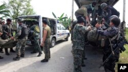Members of the Philippine National Police Special Action Forces load bodies of police commandos into vehicles in Maguindanao, Philippines, Monday, Jan. 26, 2015.