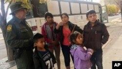 Archivo - Una familia de migrantes centroamericanos aguarda frente a un refugio en El Paso, Texas, el 29 de noviembre de 2018.