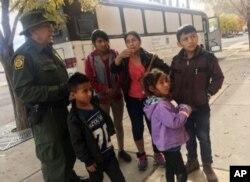 Archivo - Una familia de migrantes de Centro América espera frente a un refugio en El Paso, Texas, el 29 de noviembre, de 2018.