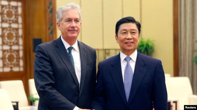 China's Vice President Li Yuanchao and U.S. Deputy Secretary of State William Burns (L) pose for a photo as they shake hands during a meeting at the Great Hall of the People in Beijing, Jan. 22, 2014.