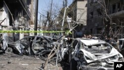 Damaged vehicles are seen at the site after two explosions near the intelligence center building in Damascus, March 17, 2012.