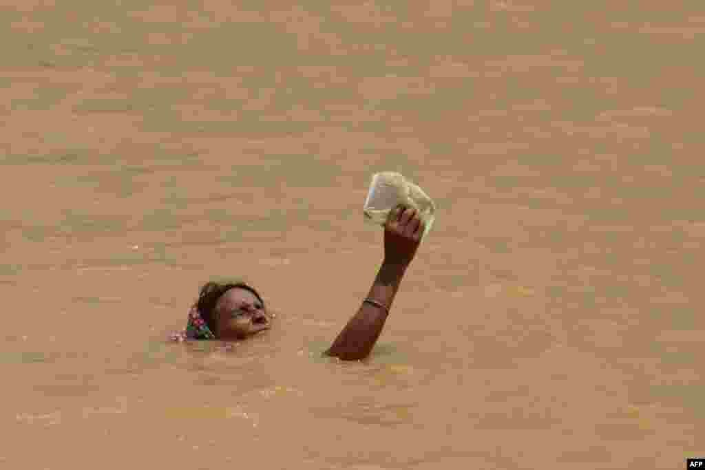 Indijka, sa nečim visoko podignutim iznad vode, što je očito željela sačuvati suhim, pokušava da se iz duboke poplave domogne plićaka.