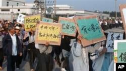 乌坎村民12月15日举着标语牌,高呼口号,要求中央政府介入