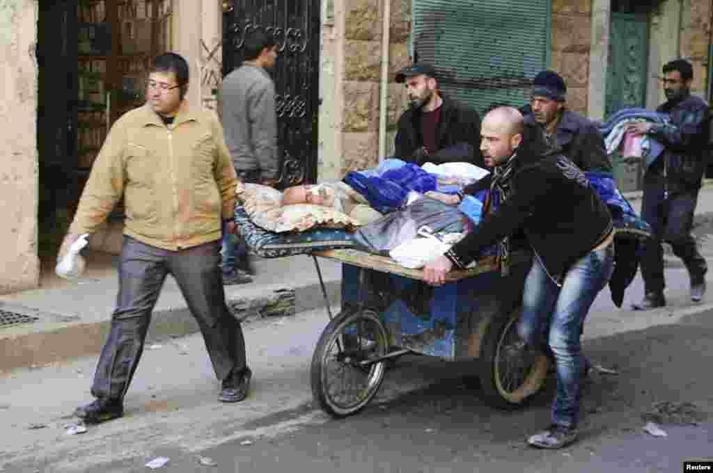 People wheel a sick man on a makeshift stretcher at the Karaj al-Hajez crossing, Aleppo, Feb. 9, 2014.