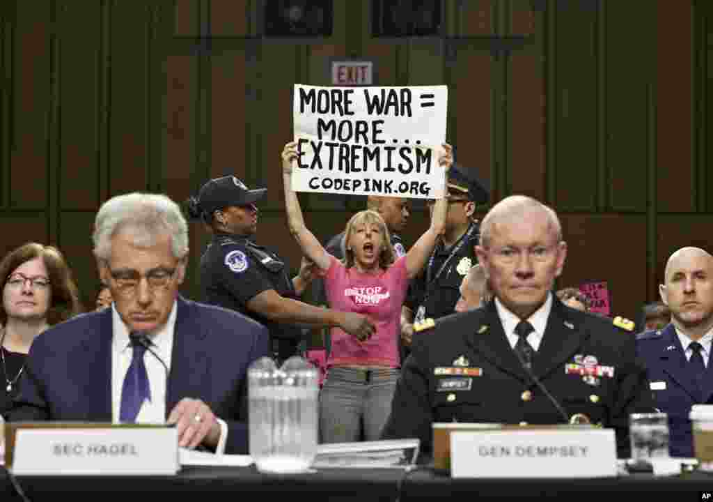Members of the anti-war activist group CodePink interrupt a Senate Armed Services Committee hearing with Defense Secretary Chuck Hagel, left, and Army Gen. Martin Dempsey, chairman of the Joint Chiefs of Staff, on Capitol Hill in Washington, DC.