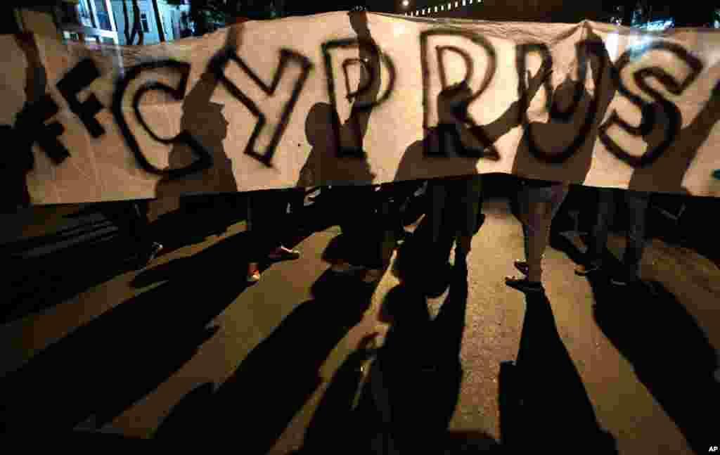 24일 키프로스 구제금융 협상이 계속되는 가운데, 의회 앞에 현수막을 설치하고 구제금융에 반대하는 시위대.