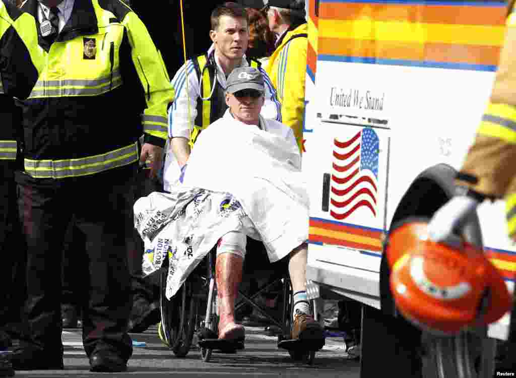 A runner in a wheelchair is taken from a triage tent after explosions went off at the 117th Boston Marathon, April 15, 2013.
