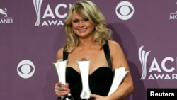 Miranda Lambert poses with her awards for female vocalist of the year, song of the year, and single record of the year backstage at the 48th ACM Awards in Las Vegas, April 7, 2013.