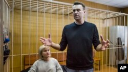 Russian opposition leader Alexei Navalny gestures while speaking, as his lawyer Olga Mikhailova listens, in court in Moscow, Russia, March 27, 2017.