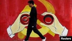 一名男子从上海街头中共党徽前走过。(2019年9月25日)