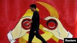 一名男子從上海街頭中共黨徽前走過。 (2019年9月25日)