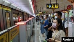 People wearing protective face masks wait for the metro, during the coronavirus disease (COVID-19) pandemic, in Taipei, Taiwan, May 11, 2021. REUTERS/Ann Wang