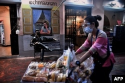 A snacks vendor wearing a mask and face shield to try to halt the spread of the Covid-19 coronavirus walks past an Elvis statue in a face mask at a market in Bangkok on January 19, 2021. (Photo by Lillian SUWANRUMPHA/AFP)