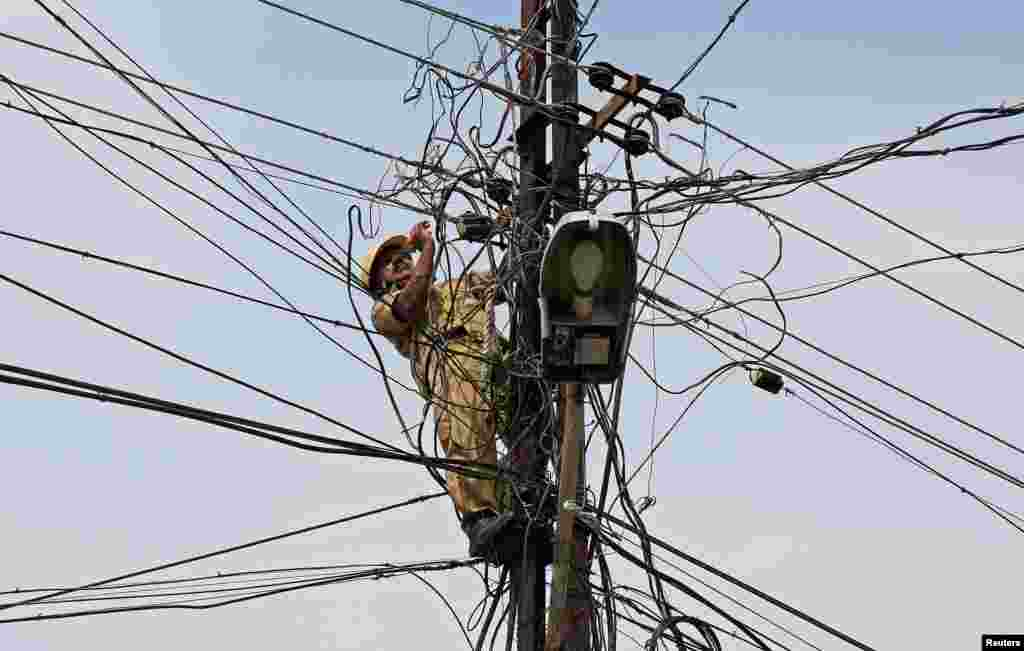 A worker repairs power lines in Kochi, India.