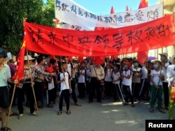 "Villagers carry banners which read ""Plead the central government to help Wukan"" (in red) and ""Wukan villagers don't believe Lin Zuluan took bribes"" during a protest in Wukan, China's Guangdong province on June 22, 2016."