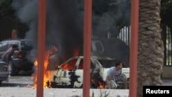 Warga di Benghazi berlindung di dekat mobil yang terbakar saat terjadi bentrokan hebat antara tentara Libya dan anggota kelompok Islamis Ansar al-Sharia di Benghazi, Libya, Senin (25/11).
