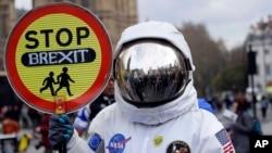 """Un manifestante vestido de astronauta muestra un cartel con el lema """"Paren el Brexit"""" durante una manifestación contra la salida del Reino Unido de la Unión Europea, en Londres, el 23 de marzo de 2019."""