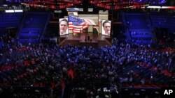 Delegates watch a video presentation during an abbreviated session of the Republican National Convention in Tampa, Florida, on Monday, Aug. 27, 2012.
