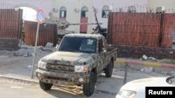 Seorang anggota pasukan keamanan yang setia kepada pemerintah Libya yang didukung PBB mengendarai pickup di penjara Al-Hadba yang rusak saat baku tembak dengan faksi saingan di distrik Abu Salim, di Tripoli, Libya, 28 Mei 2017. (Foto: Hani Amara/Reuters)