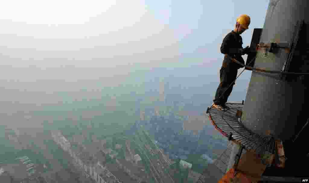 3 tháng 6: Một công nhân làm việc với một cấu trúc bằng thép trong một công trình xây dựng nhà cao tầng trong tỉnh An Huy, phía sau là làn khói do đốt rơm. (Reuters)